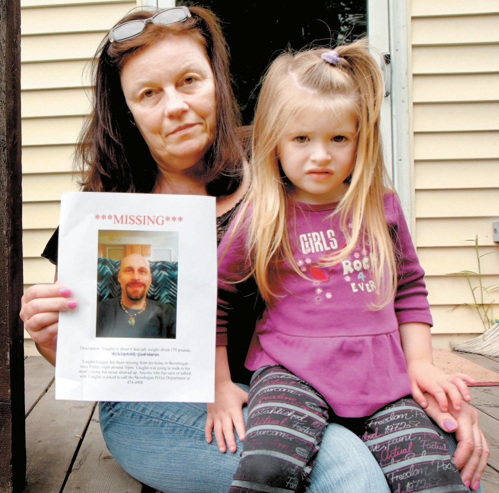 A MOTHER'S SORROW: Rosanne Dubay, mother of Vaughn Giggey, displays a photo of him after he disappeared in August while walking from his Skowhegan home to hers. With her is Giggey's niece, Arrienna Bowring. His body was found later in Currier Brook about a quarter-mile from his home on Main Street.