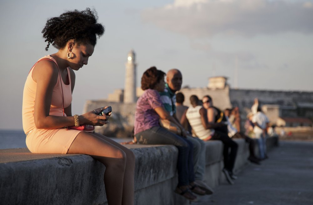 "A woman uses her cellphone as she sits on the Malecon in Havana, Cuba, recently. The U.S. Agency for International Development masterminded the creation of a ""Cuban Twitter,"" a communications network designed to undermine the communist government in Cuba, built with secret shell companies and financed through foreign banks."