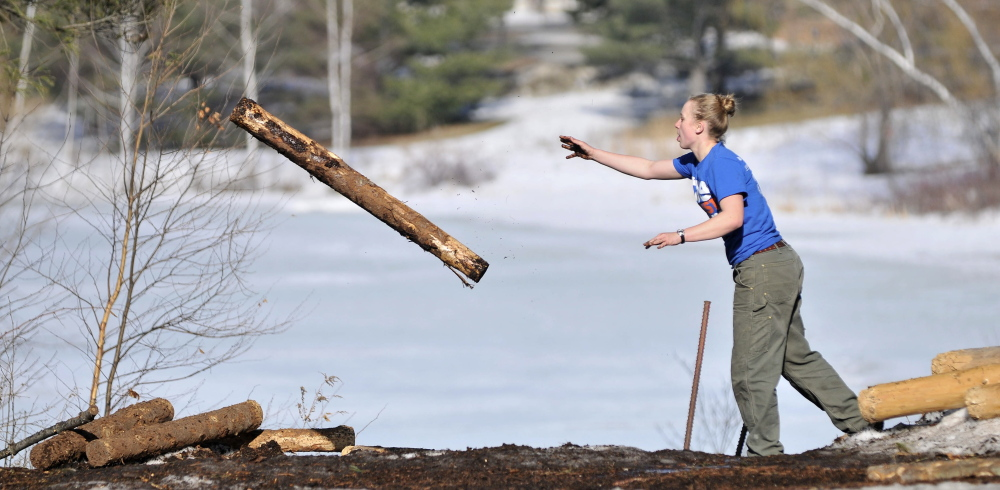 LOG TOSS: Julia Rogers, 20, a sophomore at Colby College, practices the log toss during timber sports practice at Colby College on Thursday.