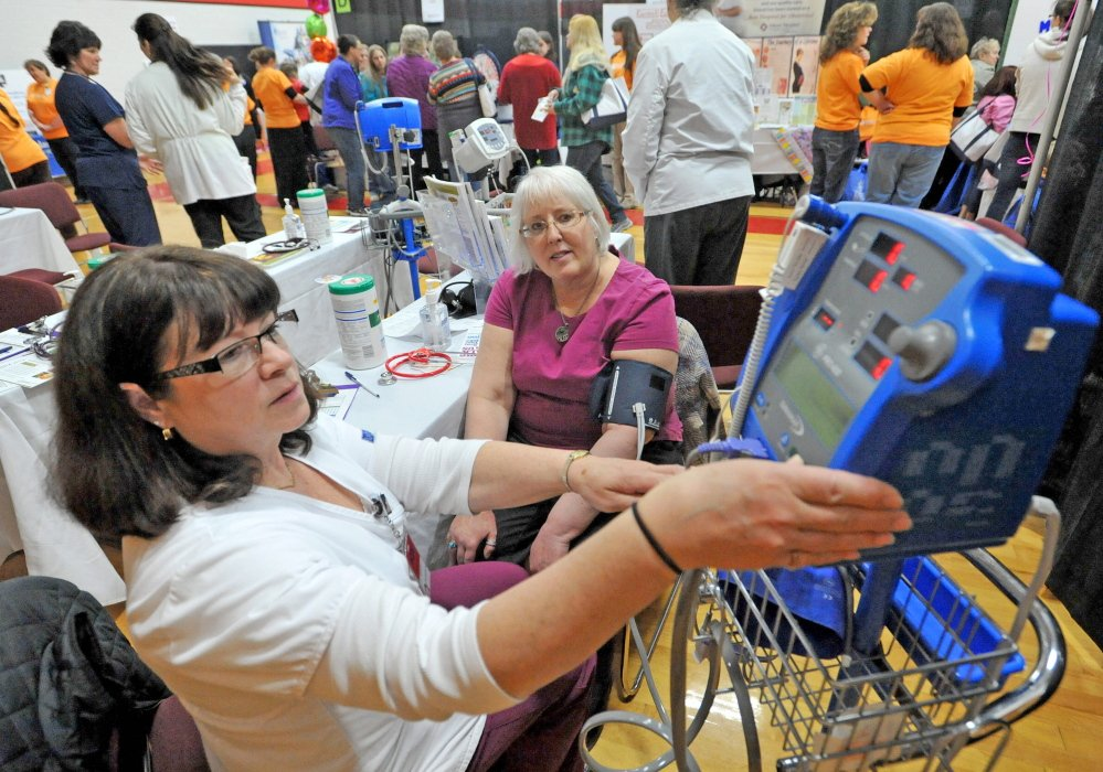 Off-the-cuff care: Vicki Goodwin, left, a registered nurse at Inland Hospital, checks the blood pressure of Connie Finley on Saturday at the 17th annual World of Women's Wellness, sponsored by Inland Hospital at Thomas College.