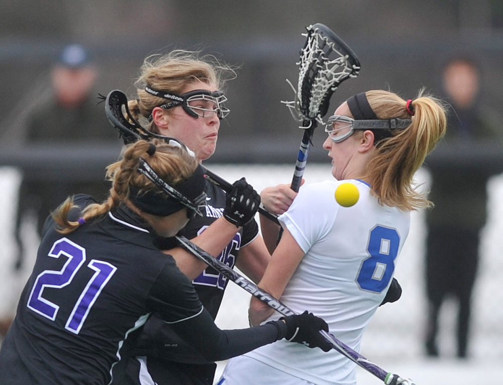 ROUGH LANDING: Colby College's Emma Marjollet (8) collides with Amherst College's Hanna Krueger (26) and Heath Cockrell in the first period at Colby College in Waterville on Saturday.