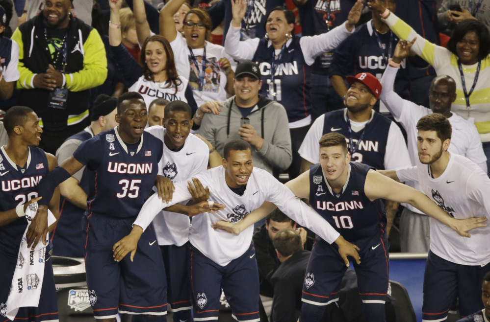 HAPPY DAYS: Connecticut players and fans begin to celebrate in the final moments of the team's 63-53 victory over Florida on Saturday during the NCAA Final Four college basketball semifinal game in Arlington, Texas.
