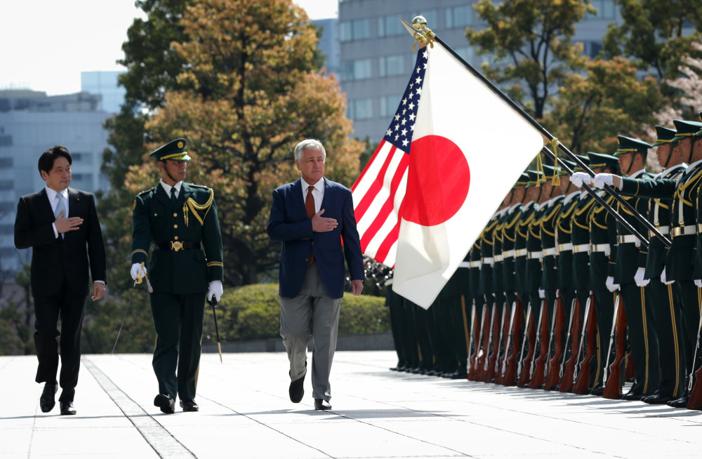 U.S. Secretary of Defense Chuck Hagel, right, accompanied by Japanese Defense Minister Itsunori Onodera, left, reviews honor guards at the Japanese Ministry of Defense headquarters Sunday.