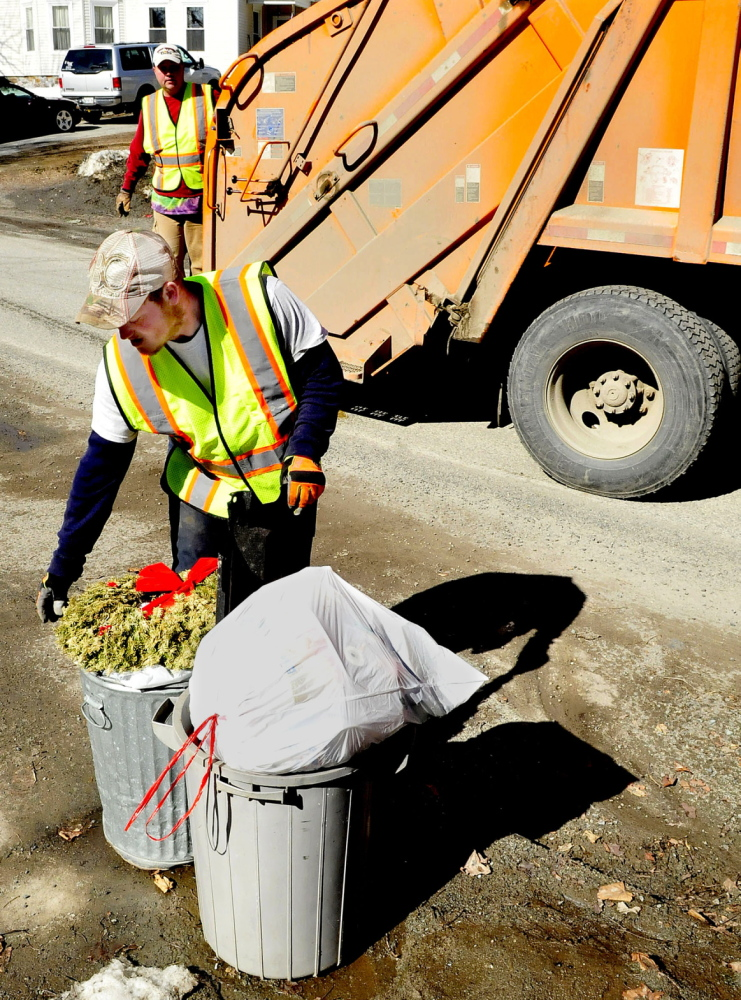 WASTE NOT: Waterville Public Works Department employees Larry Colson, front, and Brian Ames pick up trash on April 2. The city is considering alternatives to solid waste collection.