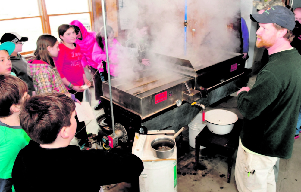 SWEET STEAM: As maple sap boils, Maine Academy of Natural Sciences teacher Jeff Chase speaks on Wednesday to Cornville Regional Charter School students, including Lydia Dore, facing at left of evaporator.