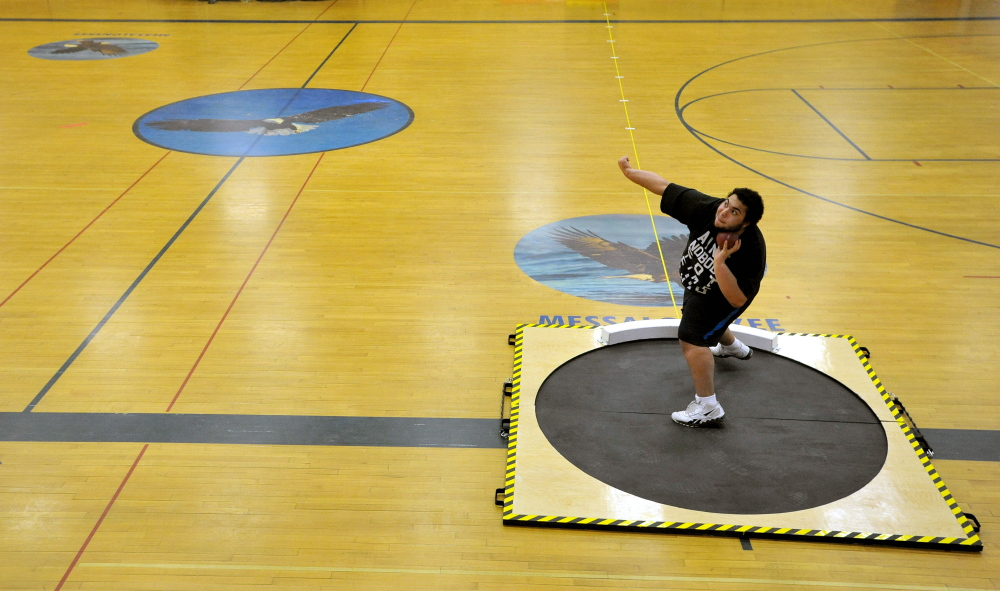 Staff photo by Michael G. Seamans Messalonskee High School senior Josh Lamontagne, 17, practices the shot-put during track practice at Messalonskee High School in Oakland.