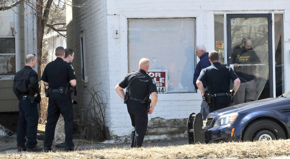 QUESTIONS: Waterville Detective Alan Perkins walks away after speaking with an occupant, in doorway, at 12 Spring St. on Thursday. Several officers and detectives surrounded the building and later arrested Peter Corson after he came out.