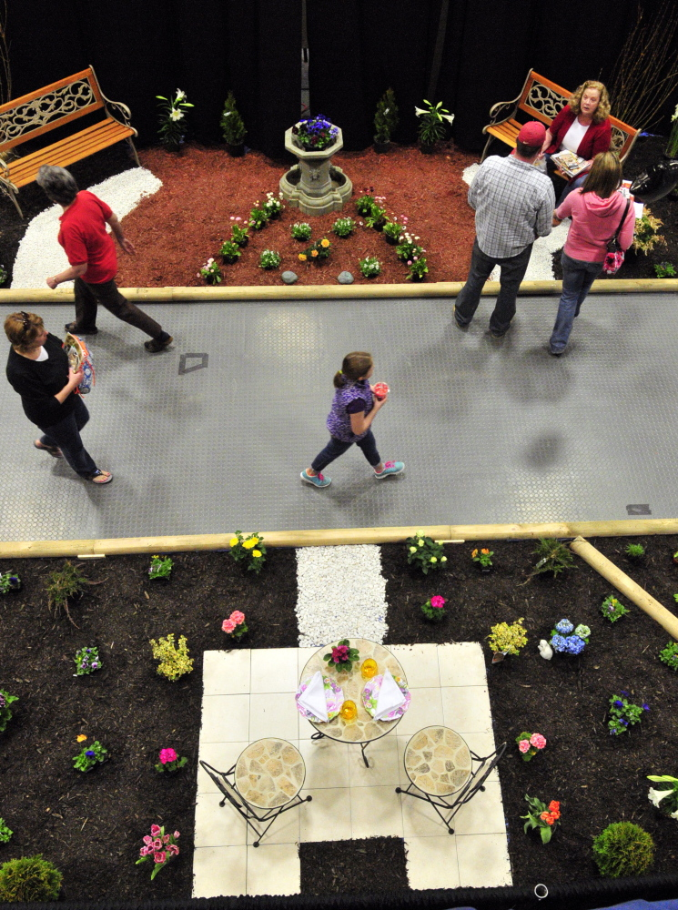 Sign of spring: People walk past displays during the Manchester Lions Home and Garden Show on Saturday at the Augusta Civic Center.