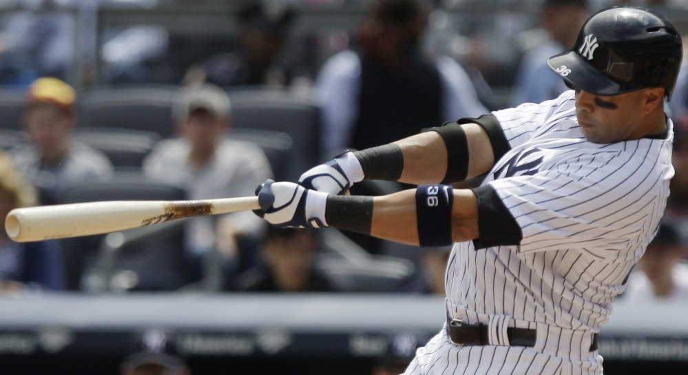 New York Yankees' Carlos Beltran follows through on a two-run home run during the first inning of a baseball game against the Boston Red Sox Saturday in New York.