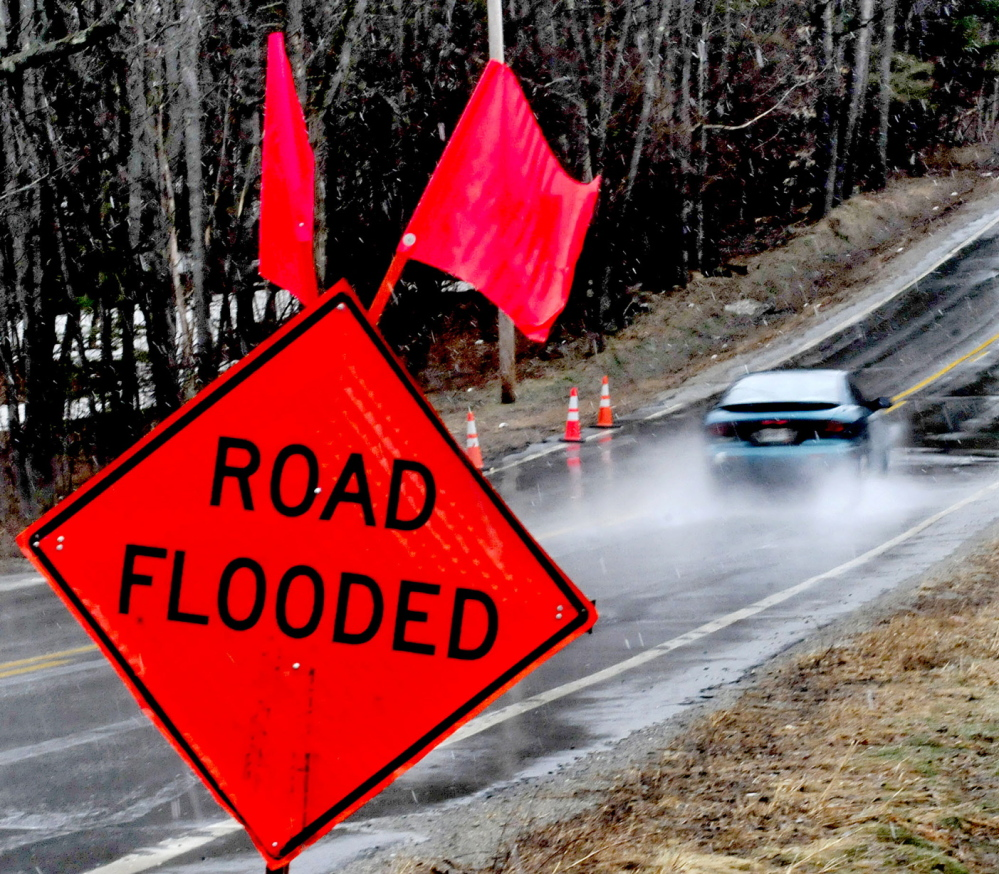 SPRING RUNOFF: A motorist drives through water that collected on the Middle Road in Skowhegan just past warning signs on a wet Sunday. The National Weather Service has issued a flood watch for many parts of the state, including Kennebec, Somerset, Franklin and Waldo counties through Wednesday evening.