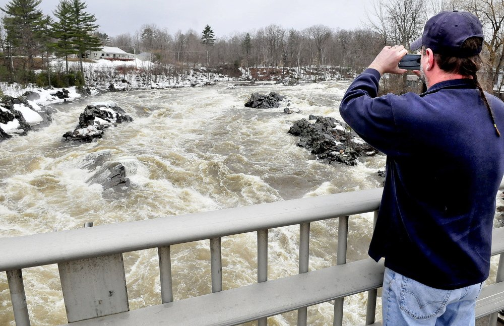 ON WATCH: Dana White,of New Portland, photographs the raging high water and ice chunks flowing down the Carrabassett River through North Anson on Tuesday.