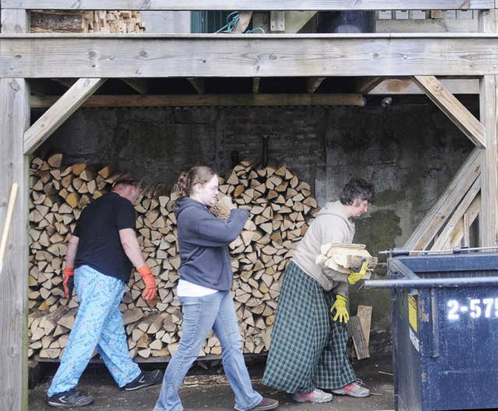Staff photo by Andy Molloy GETTING READY: Donald Hallett, left, his daughter, Cassandra, and wife, Suzette, carry kiln dried firewood Tuesday up to the first floor deck of Kennebec Pizza with Christopher Stroot ahead of a flood expected to come up over the banks of the Kennebec River. Kennebec Pizza stores the firewood for its ovens beneath the building on the shores of the River. Officials expect the river to crest Wednesday on parking lots and roads adjoining the Kennebec.