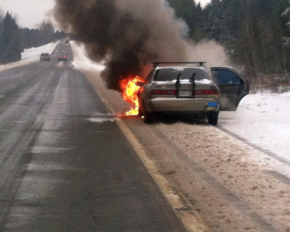 car fire: A car burns Wednesday morning on Interstate 95 in Pittsfield. Godefroy Watchiba of Portland told police he heard a loud noise under the 1999 Toyota Camry and pulled over to investigate, when it burst into flames.