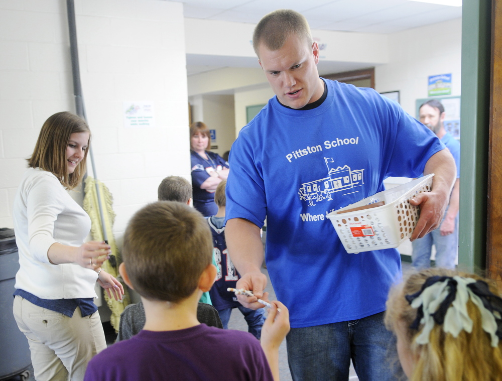 MAKING A POINT: National Football League player Matt Mulligan hands Pittston Consolidated School students pencils Wednesday. His visit was a reward for the school's participation in Fuel Up to Play 60, the NFL's nutrition and fitness initiative.
