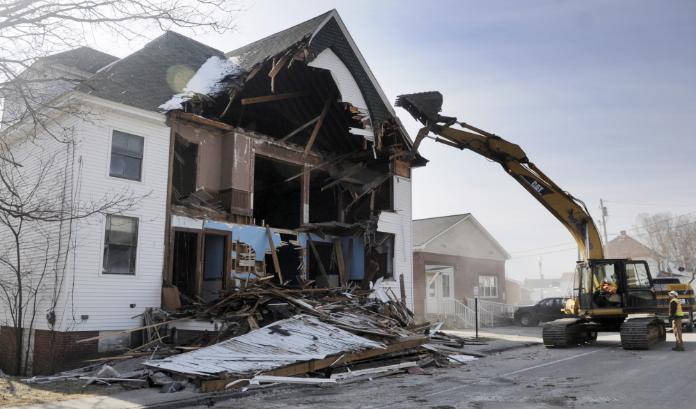 OUT WITH THE OLD: Scott McGee tears down the front of the Masonic Lodge in Winthrop on Thursday morning. McGee Construction razed the structure to make way for an expansion of C.M. Bailey Public Library.