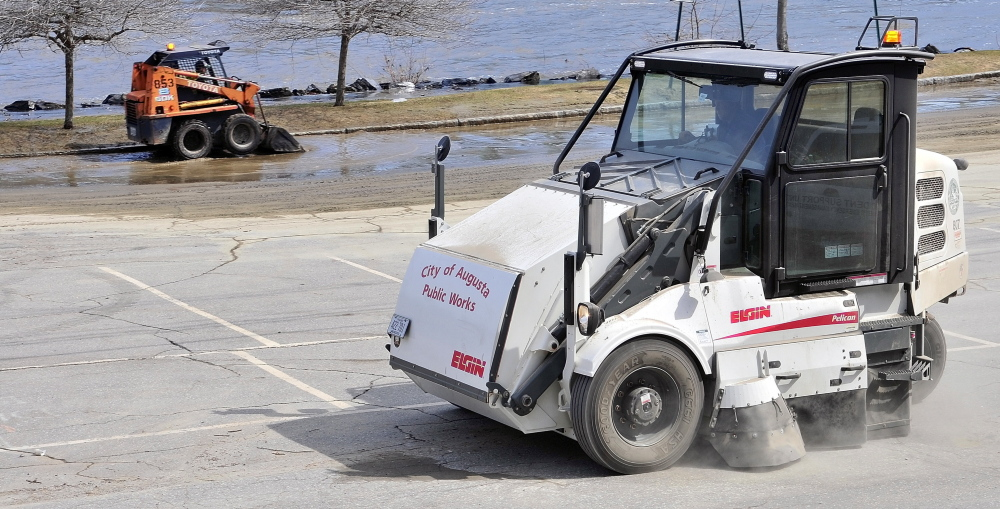 City of Augusta workers clean up the Front Street parking lot Thursday in downtown Augusta. The river had receded from the lot behind the Olde Federal Building by Thursday afternoon, but there was still water in the parking lot to the north of there.