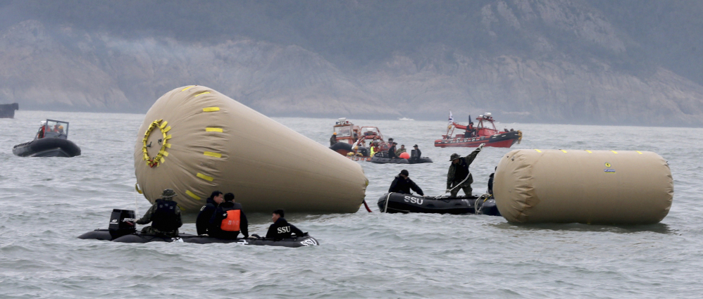South Korean navy personnel try to install buoys to mark the sunken passenger ship Sewol in the water off the southern coast near Jindo, South Korea, Friday.