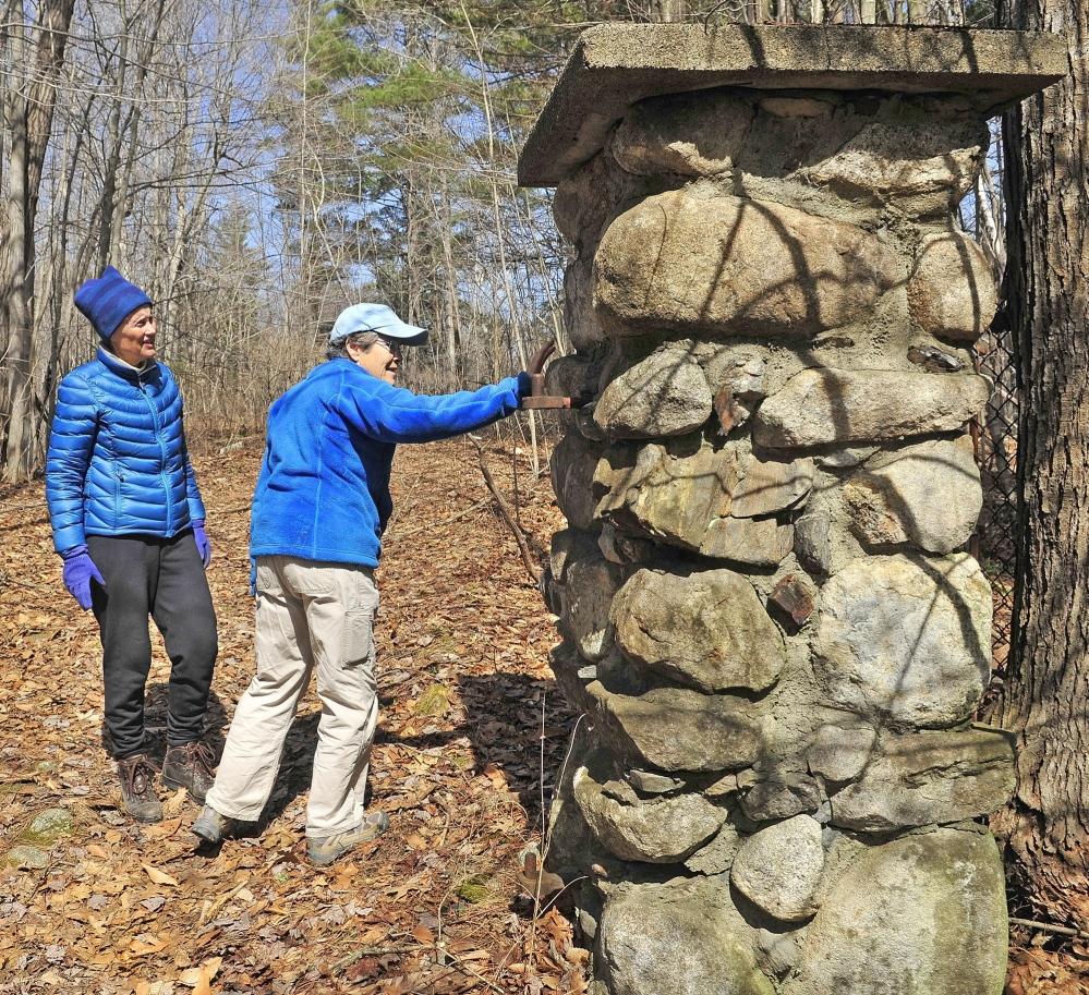 Relic of a bygone era: Sue Bell, left, and city councilor Dale McCormick look at a stone gatepost on an old carriage road leading into the former Ganneston Park during a walking tour of Howard Hill on Friday in Augusta. The wooded hill is the backdrop to the State House.