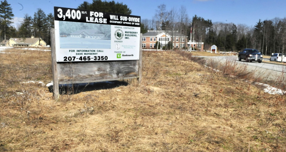 TENANTS WANTED: A sign advertising retail space stands at FirstPark in Oakland in a field beside current tenants Kennebec Veterinary Services, left, and PFBF Co.