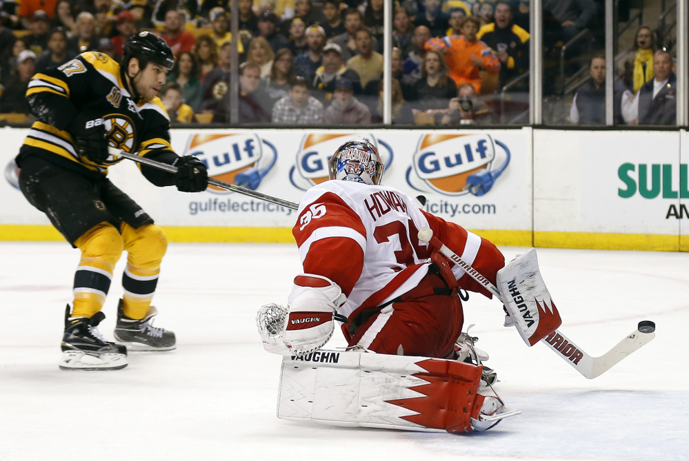 Boston Bruins' Milan Lucic, left, scores on Detroit Red Wings goalie Jimmy Howard in the second period in Boston Sunday.