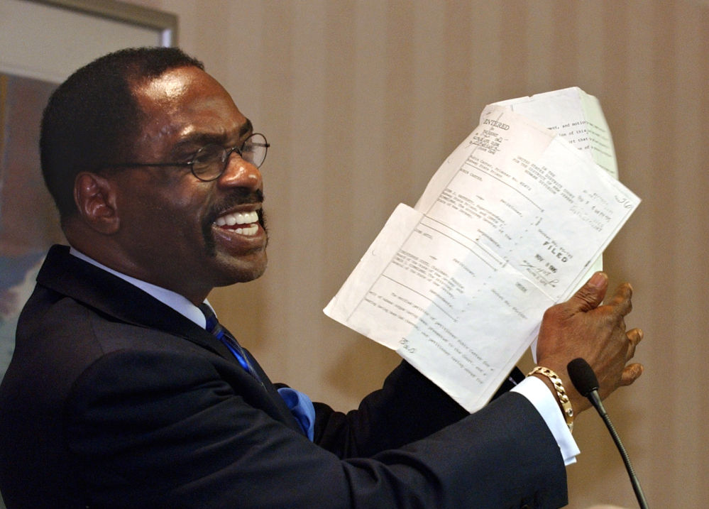 "Former boxer Rubin, ""Hurricane"" Carter, holds up the writ of habeas corpus that freed him from prison, during a news conference held in Sacramento, Calif., in January 2004. Carter, who spent almost 20 years in jail after twice being convicted of a triple murder he denied committing, died at his home in Toronto on Sunday. He was 76."