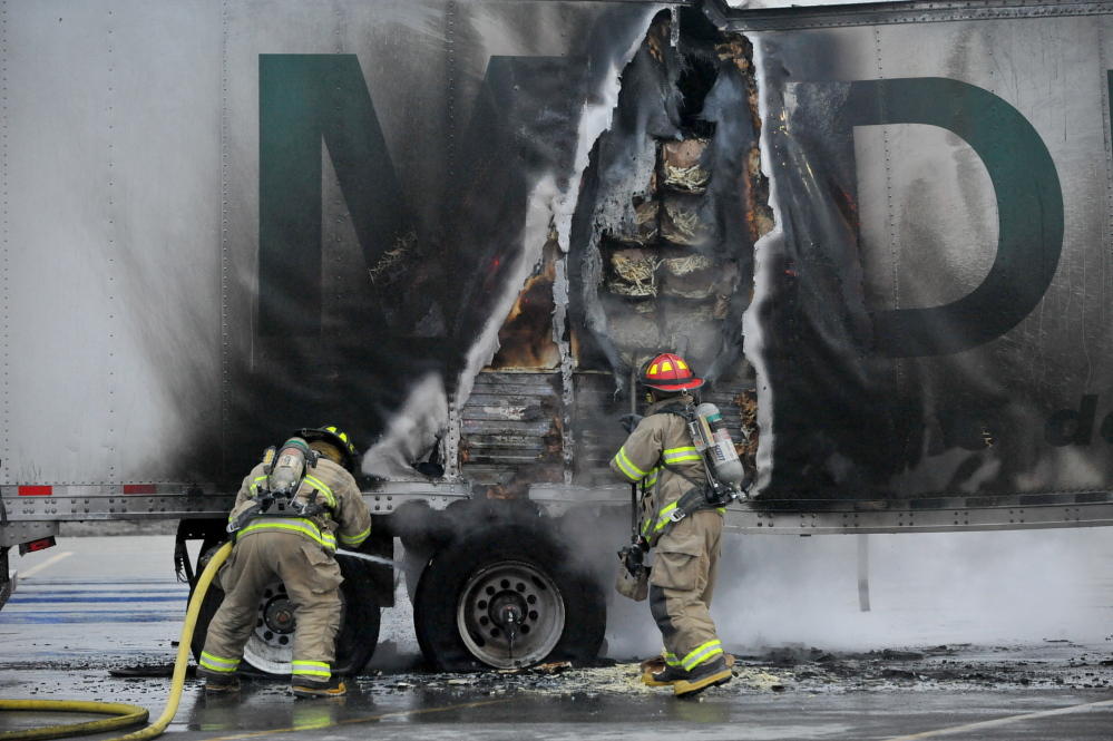 Hot brakes: Firefighters from the Waterville Fire Department extinguish a fire in a truck's trailer full of french fries in the Walmart parking lot in Waterville Tuesday evening.