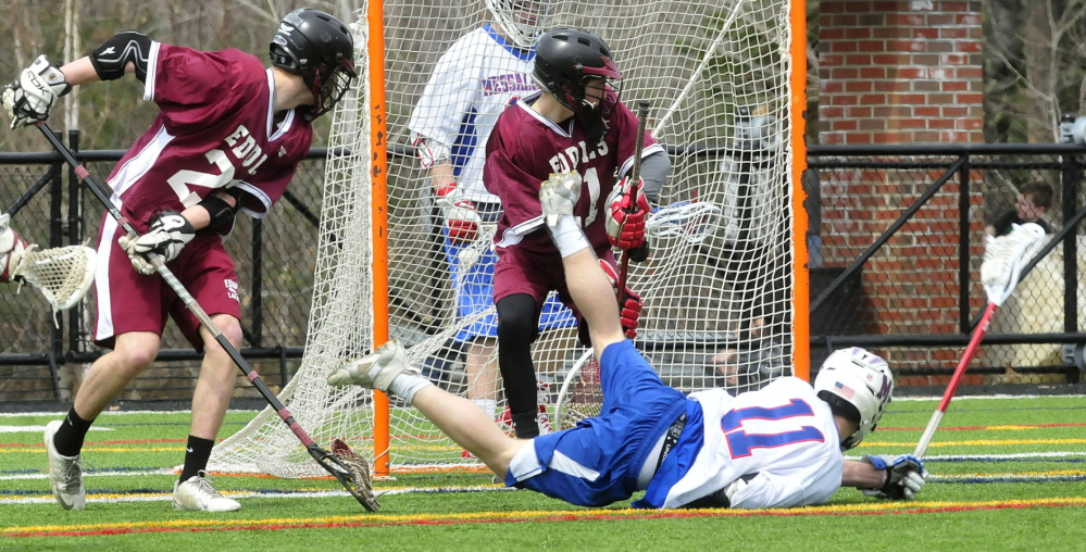 Staff photo by David Leaming Messalonskee's Josh Yonnelli falls in front of Edward Little's goalie Chris Poisson after scoring in Waterville on Tuesday, April 22, 2014.