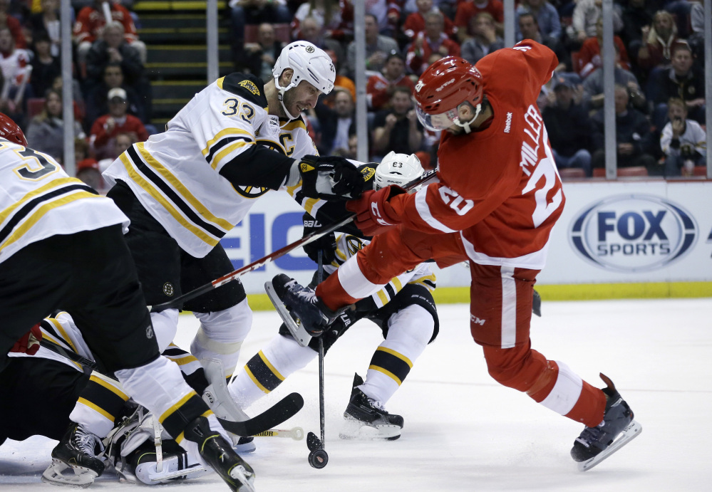 Boston Bruins defenseman Zdeno Chara (33) of the Czech Republic and Detroit Red Wings left wing Drew Miller (20) battle for the puck during the second period.