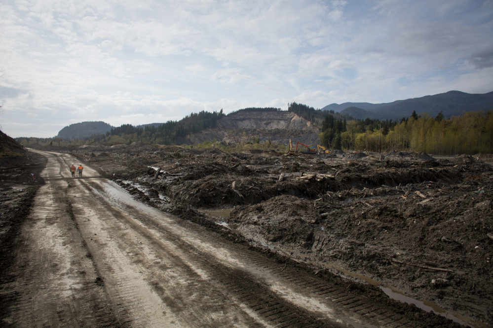 Washington Army National Guard soldiers walk along a road cut through the middle of the Oso mudslide on Monday.