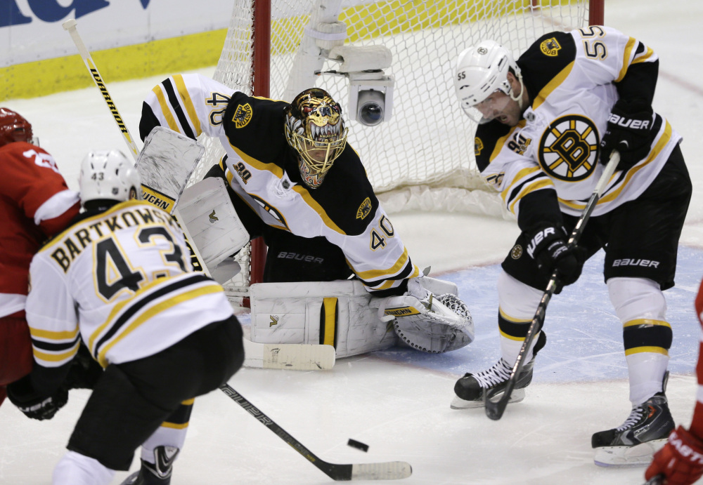 TOUGH D: Boston Bruins defenseman Johnny Boychuk (55) helps keep the puck away from Boston Bruins goalie Tuukka Rask during the third period Wednesday against the Detroit Red Wings. The Red Wings are off to their worst start offensively in the playoffs since 1945.