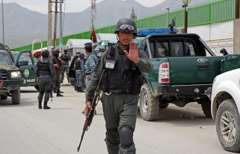 An Afghan policeman prevents journalists from approaching Cure International Hospital in Kabul, Afghanistan, Thursday.