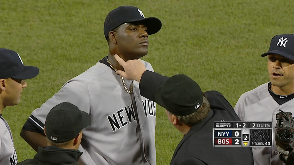 In photo taken from video and provided by ESPN, home plate umpire Gerry Davis touches the neck of New York Yankees starting pitcher Michael Pineda in the second inning of the Yankees-Red Sox game at Fenway Park Wednesday.
