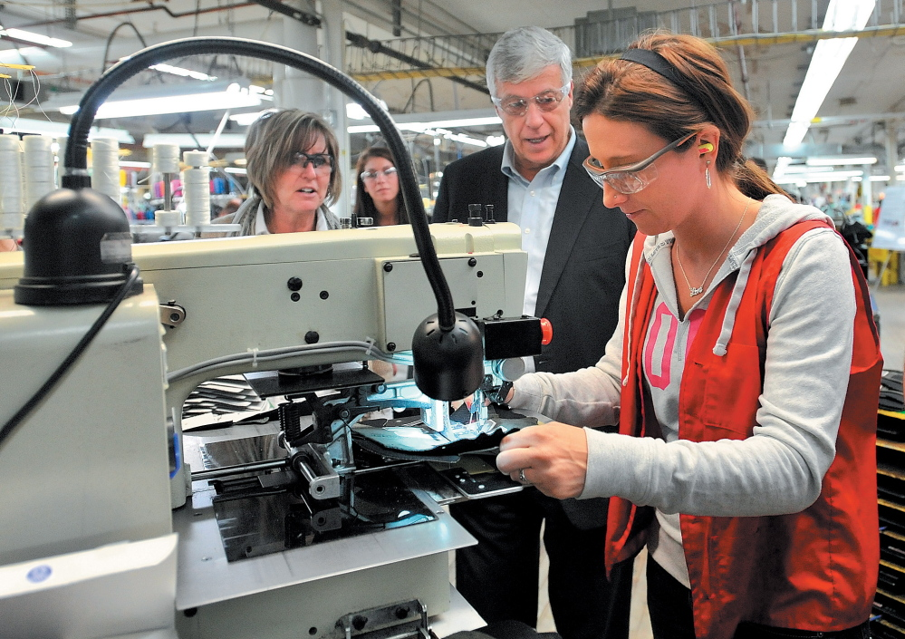 SHOE TOUR: U.S. Rep. Mike Michaud, center, speaks with New Balance factory employee while touring the shoe factory in Norridgewock in March 2012. Michaud toured the plant and picked up a pair of size 12D New Balance running shoes made at the plant for President Barack Obama.