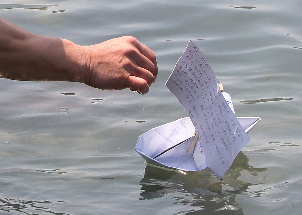A relative of a ferry passenger releases a paper boat with a message wishing for the safe return of his missing loved one in Jindo, South Korea, Friday