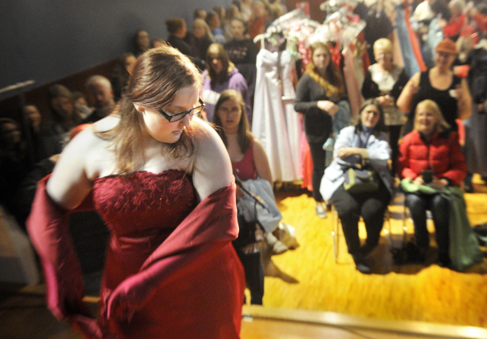 Ready in red: Cassandra Crawford, 18, of Wiscasset, displays a dress from the stage Saturday at Johnson Hall in Gardiner during the Cinderella Project. More than 100 teenage girls converged on Johnson Hall to pick up donated dresses, shoes and jewelry.
