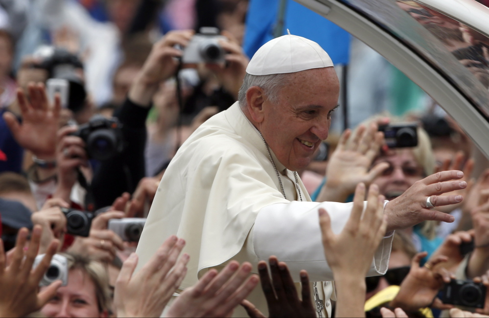 Pope Francis is driven through the crowd after presiding over a solemn ceremony in St. Peter's Square at the Vatican on Sunday. Francis proclaimed his two predecessors, John XXIII and John Paul II, saints.