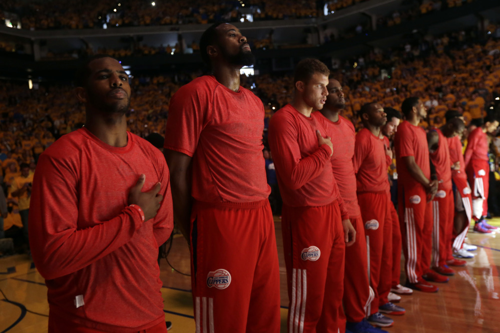 Members of the Los Angeles Clippers listen to the national anthem before Game 4 of an opening-round NBA basketball playoff series against the Golden State Warriors on Sunday.