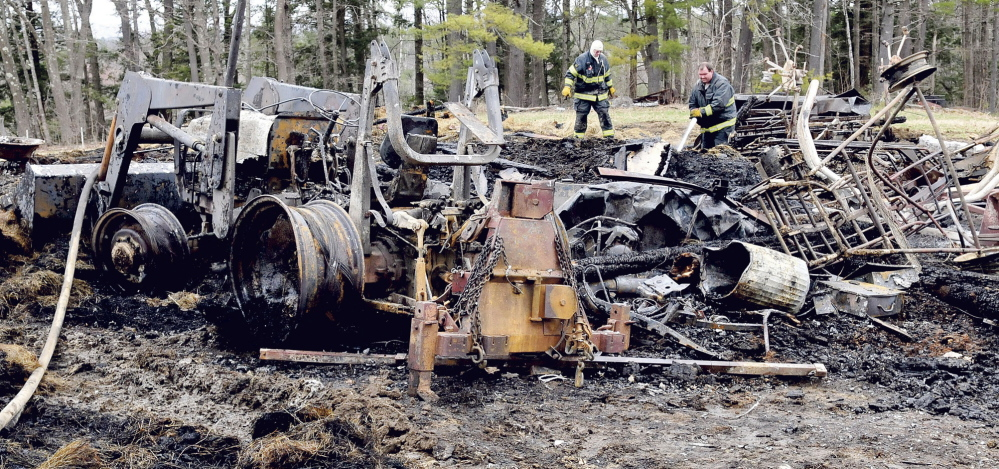 FATAL FIRE: Norridgewock firefighters James Gordon, left, and Ryan Jones hose down hot spots in the burned remains of a barn on Elm Street in Mercer on Monday, April 28, 2014. Owner Jason Hilton said the fire started in the early morning and believes the cause is electrical. A horse and three goats died and farm equipment was destroyed.