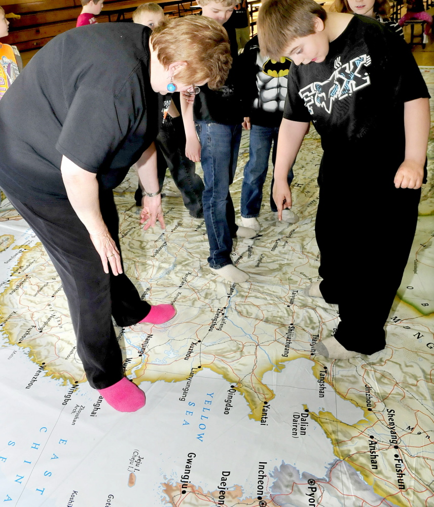 GROUNDED: Sue Lahti, of the Farmington-based Maine Geographic Alliance, points Garrett Schenck School student Nicholas Gower to a province in Asia on a giant map at the Anson school on Tuesday.