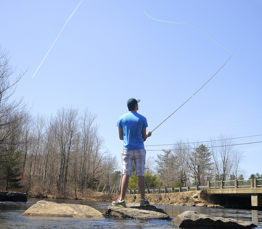 EARLY START: Michael Siddall casts a fly line for the first time April 20 on Cobbossee Lake in Manchester. Siddall, 18, of Winthrop, accompanied his father, Chris, on the outing. The lake didn't officially have ice out until April 22.