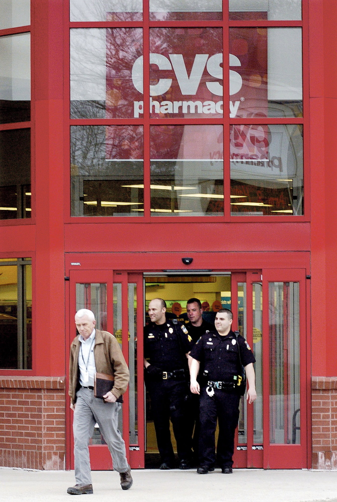 BAD CALL: Waterville police including, from left, Detective Alan Perkins, Sgt. Brian Gardiner and officers Damon Lefferts and Kyle McDonald exit the CVS store in Waterville on Wednesday after responding to a bomb threat. The building was searched and nothing was found.