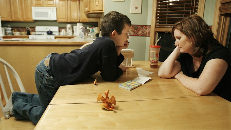 In this 2006 file photo, Nicholas Chamernik, 9, shows his mom, Aimee, some of his Pokemon stickers. More women are staying at home full-time to raise their children, according to a new Pew Research Center report released Tuesday.