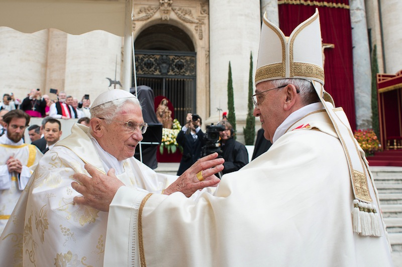 In this photo provided by the Vatican newspaper L'Osservatore Romano, Pope Francis, right, embraces his predecessor Pope Emeritus Benedict XVI, during a ceremony in St. Peter's Square at the Vatican on Sunday.