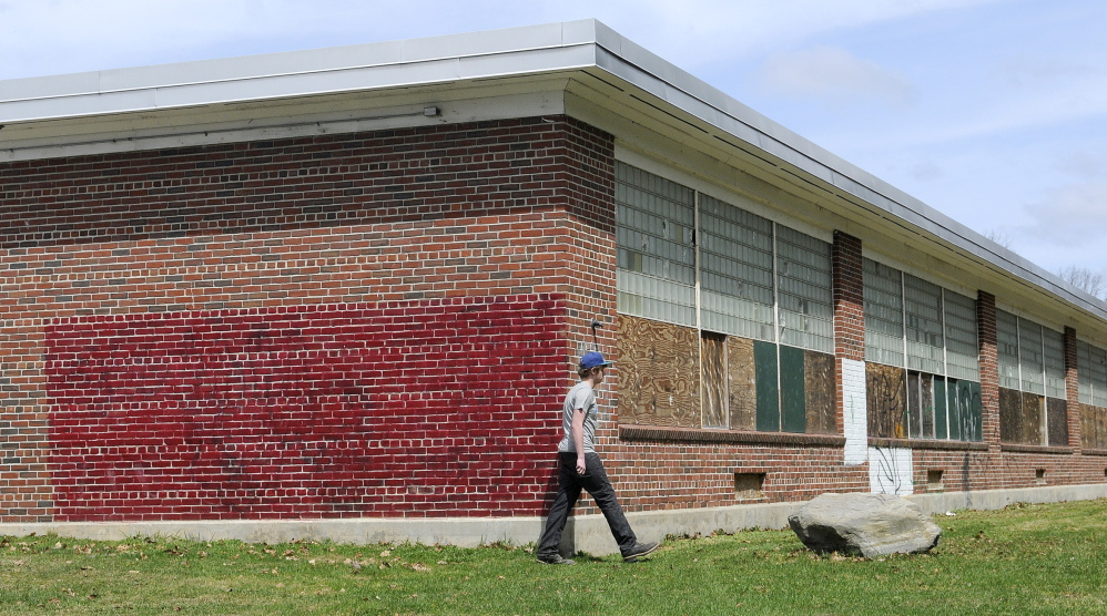 FUTURE HOUSING: Tyler Lessard, 15, walks Tuesday around the former Hodgkins Middle School in Augusta to the nature trails behind it. The Augusta City Council Thursday night approved the first step in turning the vacant building into senior housing.