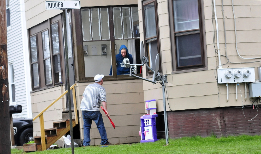 GLASS: A man uses a toy shovel to scoop up large pieces of glass from a broken window on Clinton Avenue in Winslow on Thursday. A man was injured after he broke windows and damaged doors with a snow shovel at the apartment building.