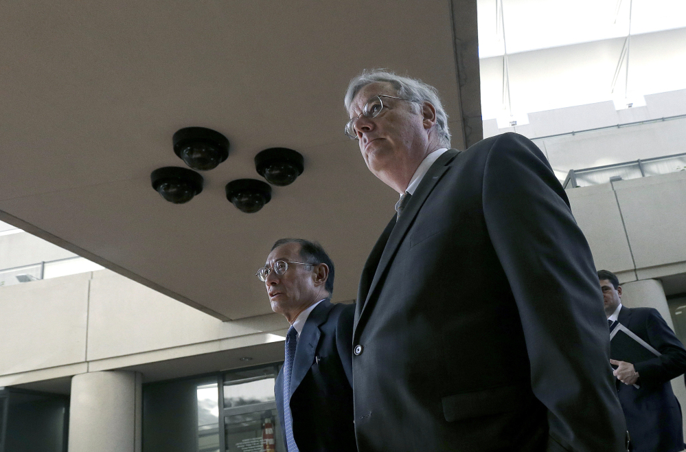 In this Tuesday, April 29, 2014, file photo, Apple attorneys Harold McElhinny, foreground, and William Lee walk to a federal courthouse in San Jose, Calif., Tuesday.