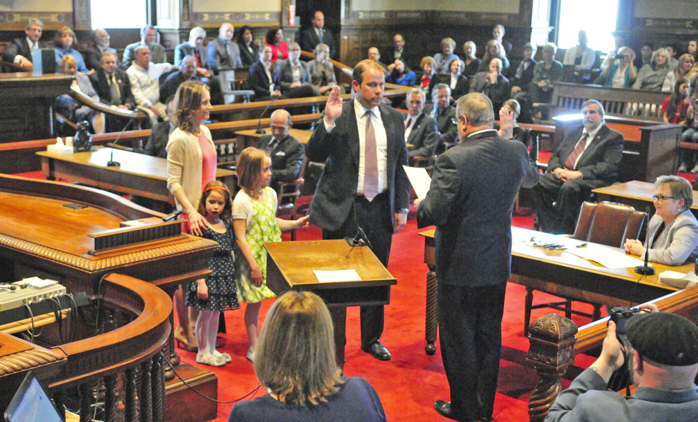 ROBING CEREMONY: Lance Walker, center, is sworn in as district court judge by Gov. Paul LePage during a swearing in ceremony on Friday at Kennebec County Superior Court in Augusta. His wife, Heidi Walker, left, and their children Dylan and Ava wait to put on his robe when he finishes the oath.