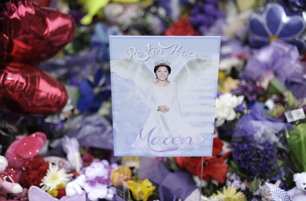 A sign with a photograph of Maren Sanchez stands among a flowers left at a memorial rock for Sanchez at Jonathan Law High School in Milford, Conn., on Friday. Sanchez was fatally stabbed inside the school last Friday hours before her junior prom.