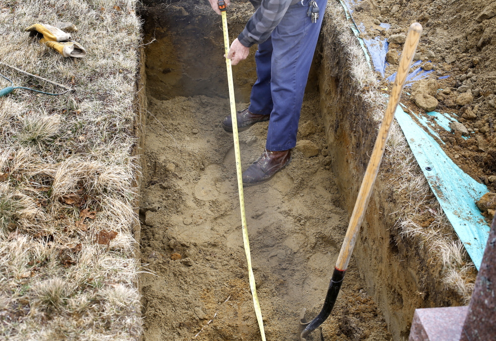 """Everard Hall measures the length of a grave in a cemetery in Cherryfield on April 25. """"I'm out in the cemetery digging a grave. God is with me every day,"""" he says."""