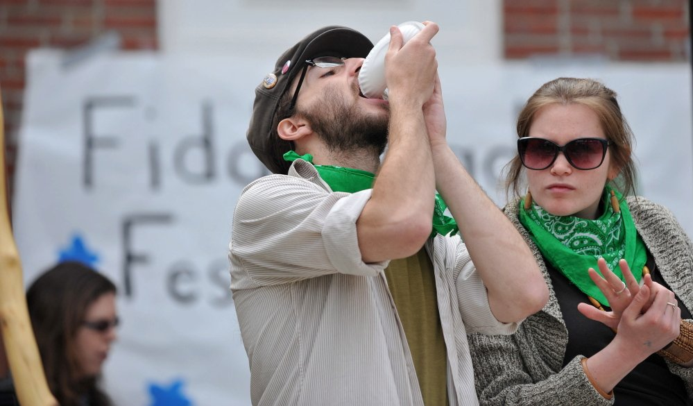 Delicious: Kyle Sareyani, left, finishes a plate of lemon avocado fiddlehead flatbread at the third annual Fiddlehead Festival in Farmington on Saturday.